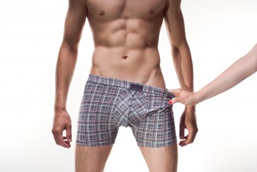 Right hand stripping male boxers for a woman